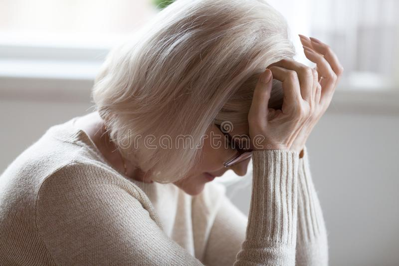 Elderly woman feeling unwell suffering from pain or dizziness. Tired elderly woman suffer from severe headache sitting with eyes closed, exhausted senior female royalty free stock photos