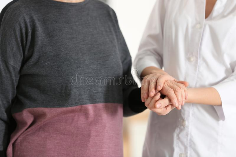 Elderly woman with female caregiver on blurred background. Closeup view stock photography