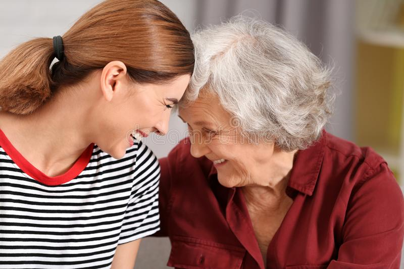 Elderly woman with female caregiver. Elderly women with female caregiver on blurred background stock photo
