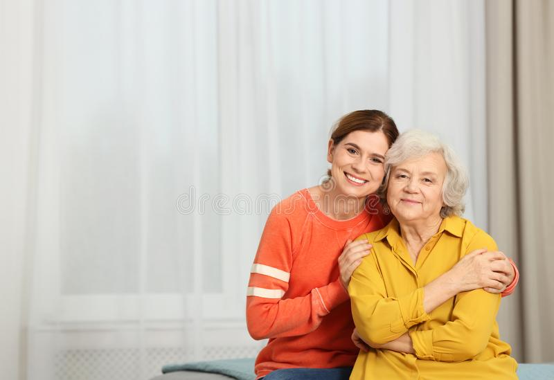 Elderly woman with female caregiver at home. Elderly women with female caregiver at home. Space for text stock images