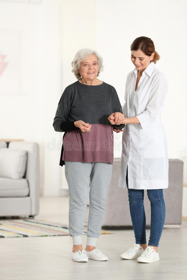 Elderly woman with female caregiver. Elderly women with female caregiver in living room royalty free stock photos