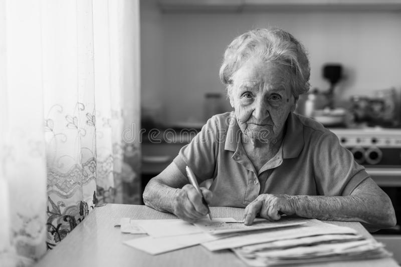 Elderly woman fills out utility bills sitting in the kitchen. Black-and-white photo royalty free stock photography