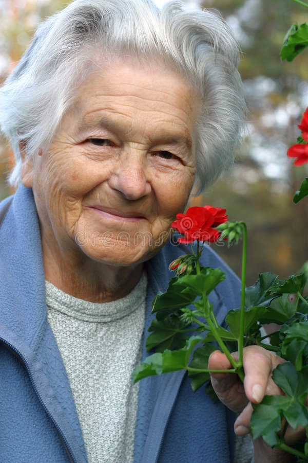 Elderly woman and flowers stock images