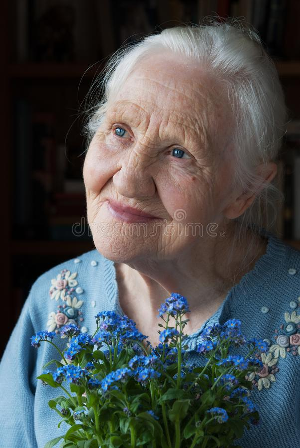 Elderly woman with flowers stock images