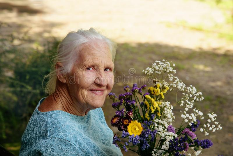 Elderly woman with flowers royalty free stock photos