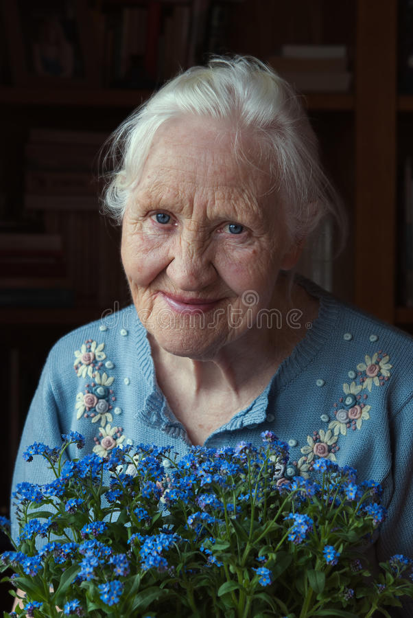 Elderly woman with flowers royalty free stock photo
