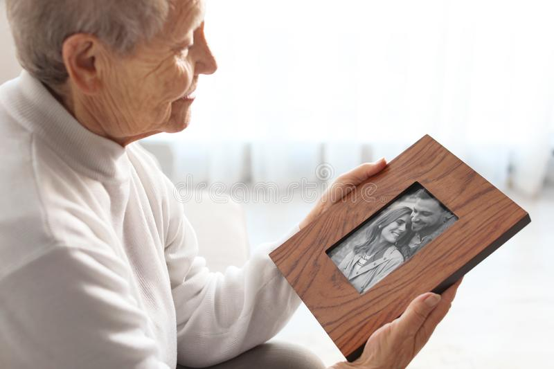 Elderly woman with framed family portrait stock photo