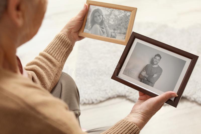 Elderly woman with framed photos royalty free stock photography