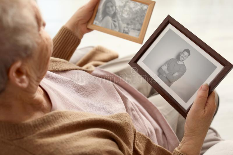 Elderly woman with framed photos royalty free stock image