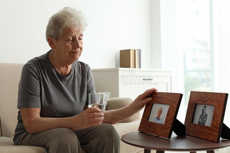 Elderly woman with framed photos royalty free stock photo