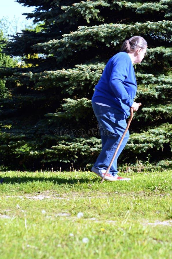 An elderly woman in the garden. An elderly woman with a cane in the garden stock photos