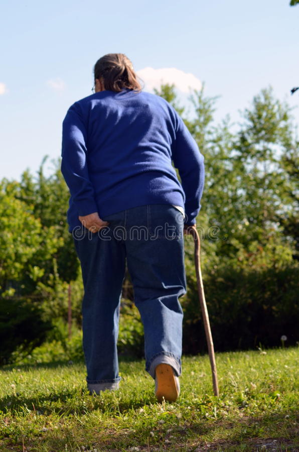 An elderly woman in the garden. An elderly woman with a cane in the garden stock images