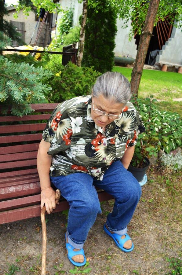 An elderly woman in the garden. An elderly woman with a cane in the garden on the bench stock photos