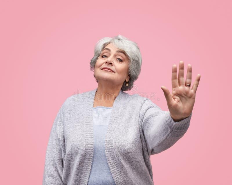 Elderly woman gesturing stop stock photo