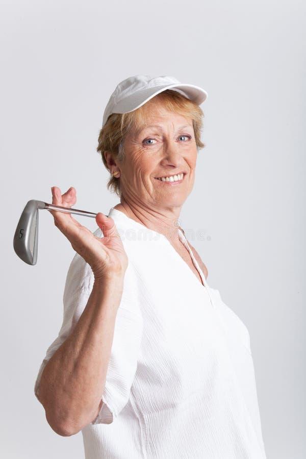 Elderly woman with a golf club stock photos