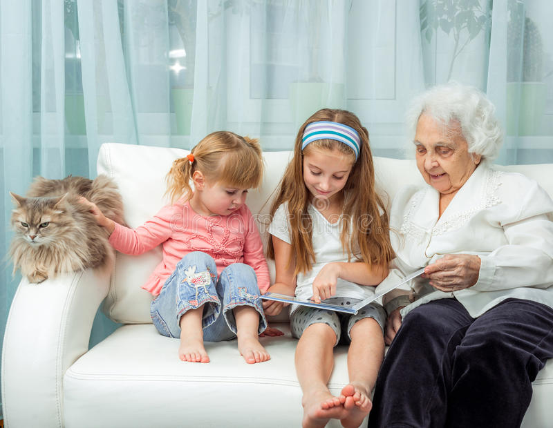 Elderly woman with granddaughters reading book. Elderly women with granddaughters reading book on sofa with cat stock photo