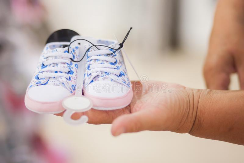 Elderly woman grandmother choosing baby clothes in the shop. Elderly woman in baby apparel store, buying tiny shoes for the newborn child, grandmother concept royalty free stock images