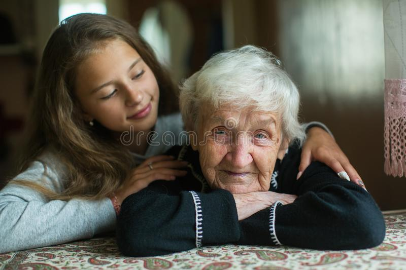 An elderly woman grandmother with her little girl granddaughter. Love. An elderly women grandmother with her little girl granddaughter stock images