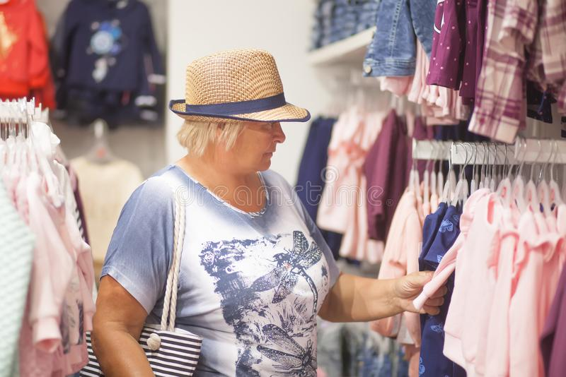 Elderly woman choosing baby clothes in the shop. royalty free stock image