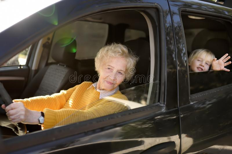 An elderly woman, grandmother or nanny, is driving a child in a car to kindergarten. Grandmother`s upbringing stock photography