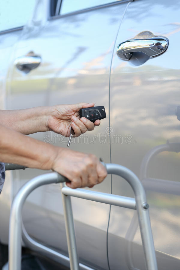 Elderly woman hand open the car on key. Car alarm systems royalty free stock image