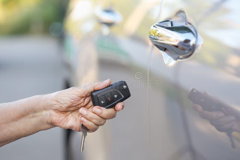 Elderly woman hand open the car on key car. Alarm systems stock photos