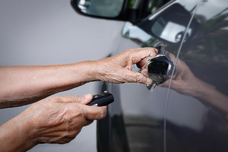 Elderly woman hand open the car on key systems. Elderly woman hand open the car on key car alarm systems stock photos