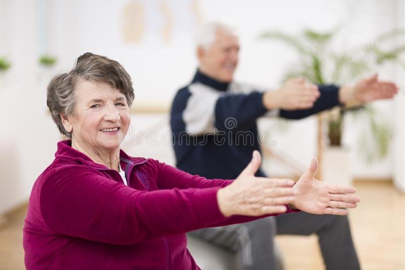 Elderly woman happily exercising with her friend during pilates for seniors royalty free stock image