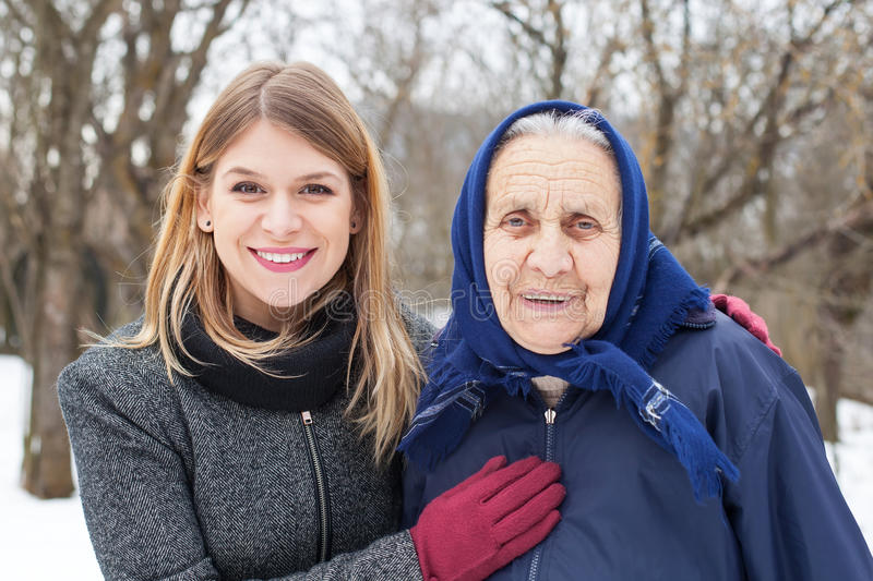 Elderly woman with her caretaker. Picture of a cute elderly women with her helping caretaker royalty free stock images