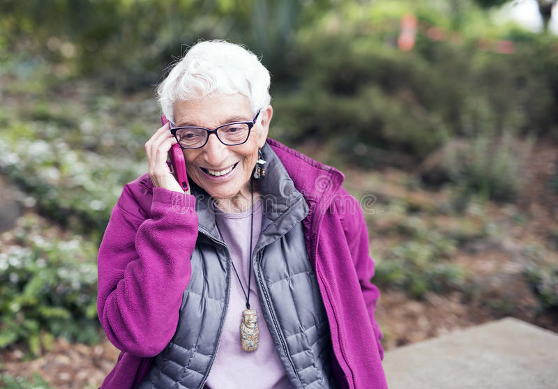 Elderly Woman in her Eighties on Mobile Phone in Park stock photo
