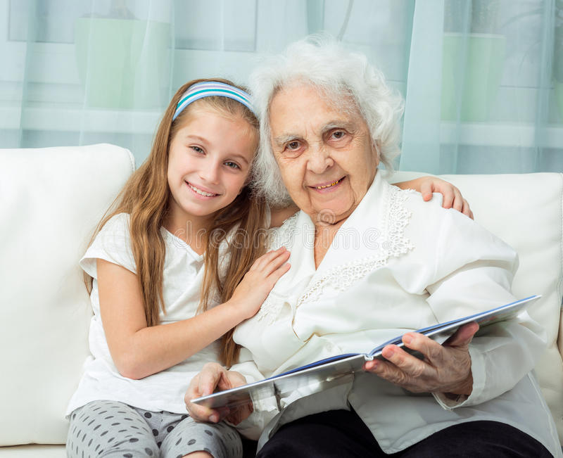 Elderly woman and her granddaughter with book. Elderly women with granddaughter with book on sofa royalty free stock image