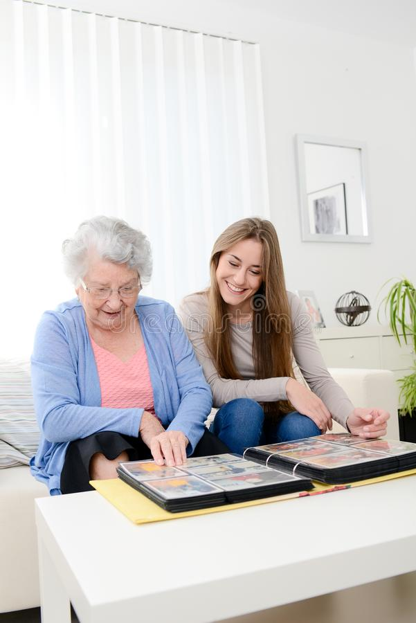 Elderly woman with her young granddaughter at home looking at memory in family photo album. Elderly women with her young granddaughter at home looking at memory royalty free stock image