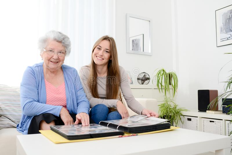 Elderly woman with her young granddaughter at home looking at memory in family photo album. Elderly women with her young granddaughter at home looking at memory stock photos