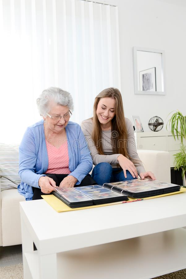 Elderly woman with her young granddaughter at home looking at memory in family photo album. Elderly women with her young granddaughter at home looking at memory stock images
