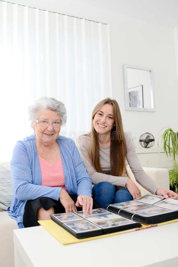 Elderly woman with her young granddaughter at home looking at memory in family photo album. Elderly women with her young granddaughter at home looking at memory stock photo