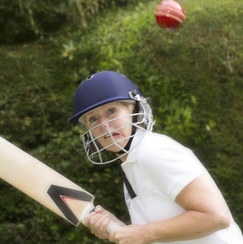 Elderly woman hitting cricket ball royalty free stock photography