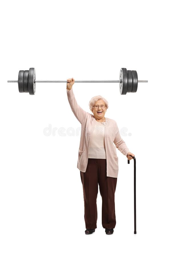 Elderly woman holding a barbell and a cane stock photography