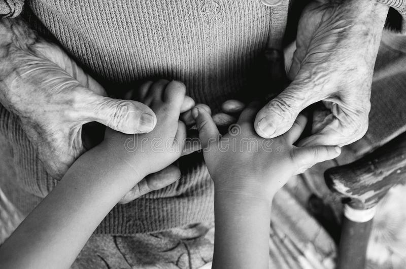 An elderly woman holding children`s hands, a wooden cane on the street. great-grandmother and great-grandson.black and white phot stock photography