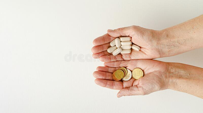 Elderly woman holding euro coins and pills in her hands. financial problems concept royalty free stock photo