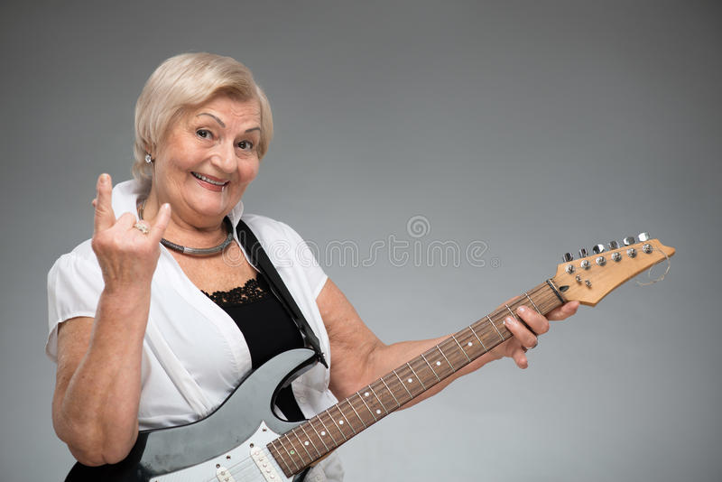 Elderly woman holding the guitar royalty free stock photos