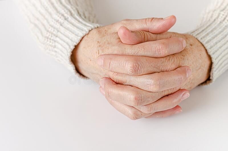 An elderly woman holding hand together on white background. Close up. Copy space royalty free stock photography