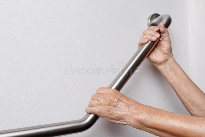 Elderly woman holding on handrail for safety steps stock photo