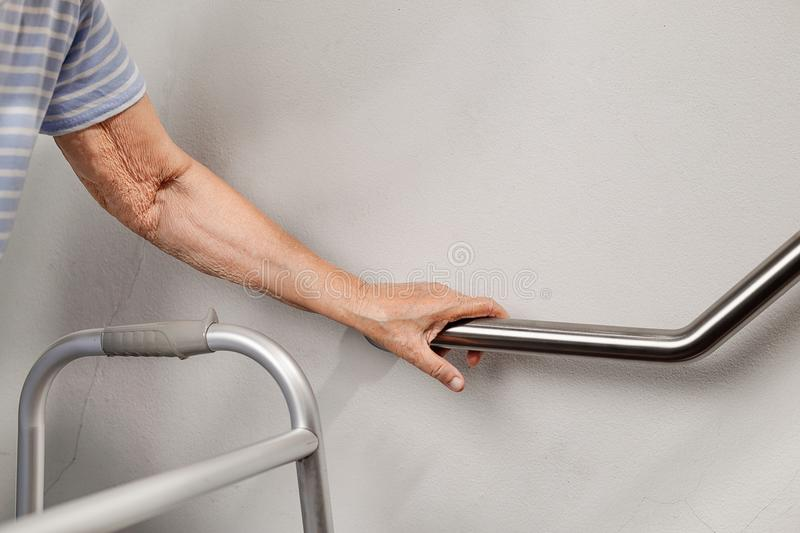 Elderly woman holding on handrail for safety steps stock image