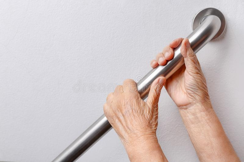Elderly woman holding on handrail for safety steps royalty free stock photography