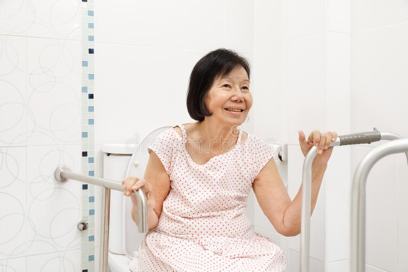 Elderly woman holding on handrail in toilet. stock photos
