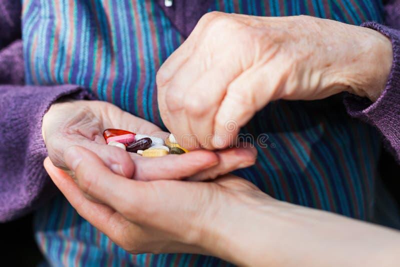 Elderly woman holding medical drugs stock photo