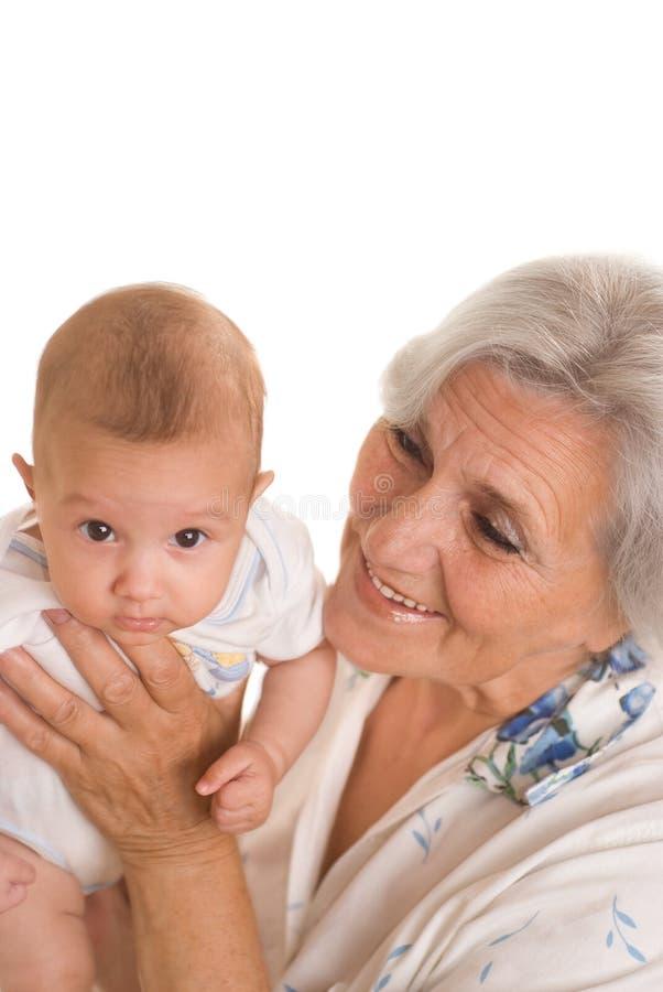 Elderly woman holding a newborn royalty free stock photos