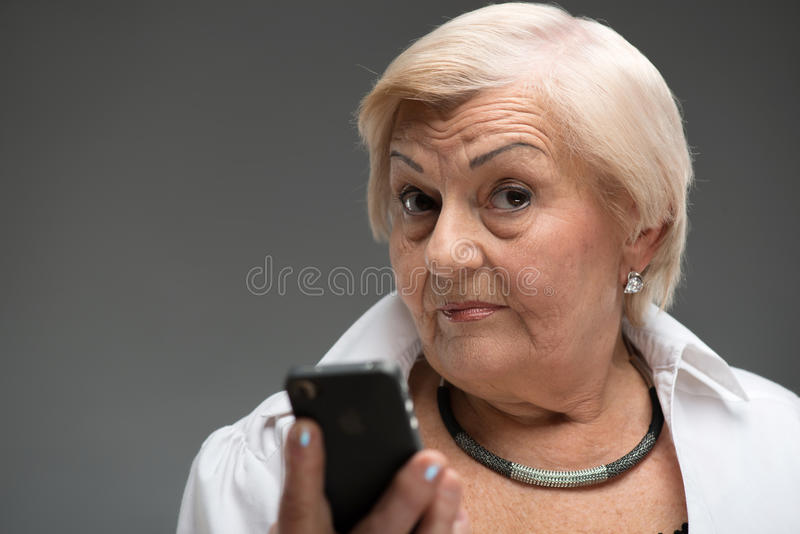 Elderly woman holding smartphone stock images