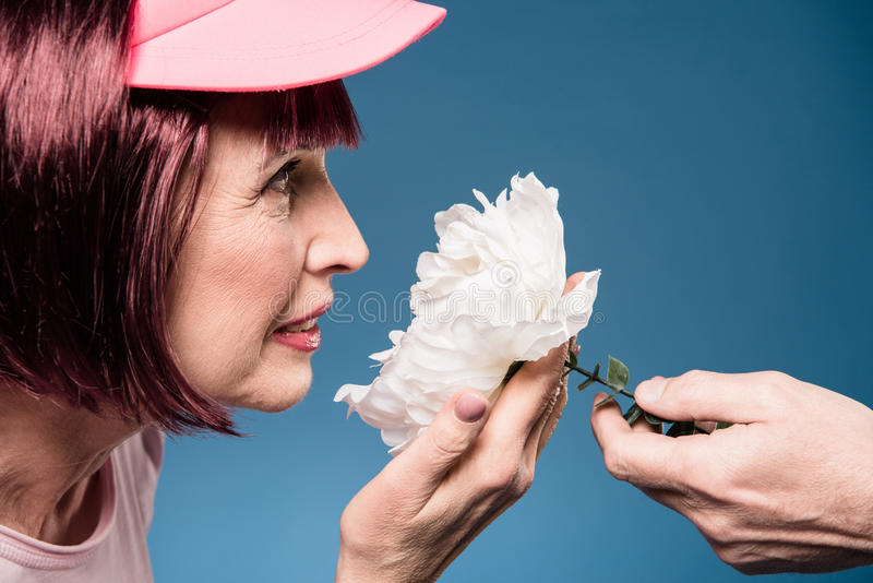 Elderly woman holding and smelling white flower royalty free stock images