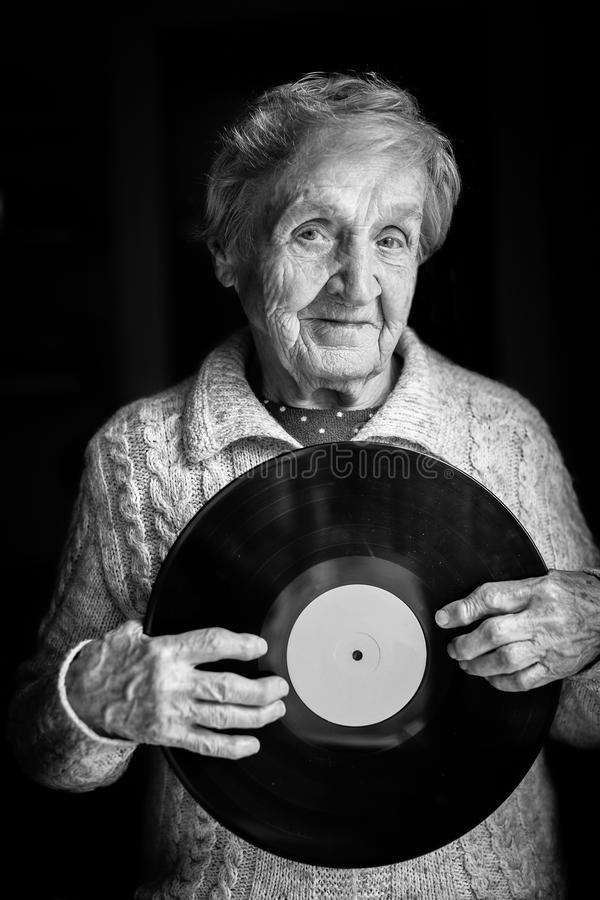 Elderly woman is holding a vinyl record. Black and white photo stock photos